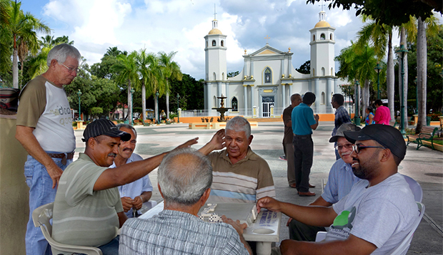 men playing dominos in the plaza in front of the GUayama church